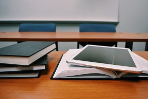 Tablet on desk with books